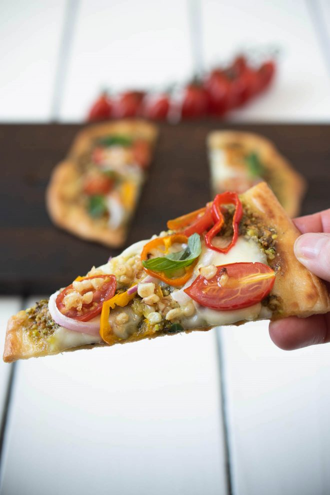 Holding a slice of the flatbread pizza