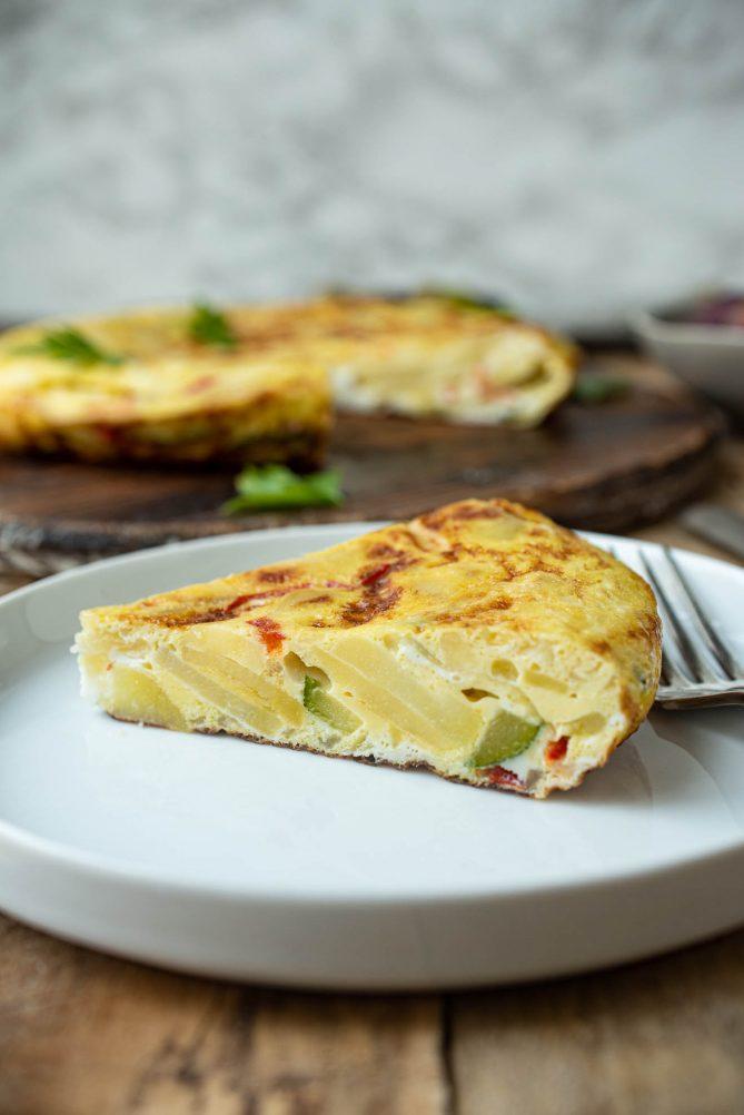 A slice of Spanish omelette on a plate viewed from the side showing the colorful vegetables inside