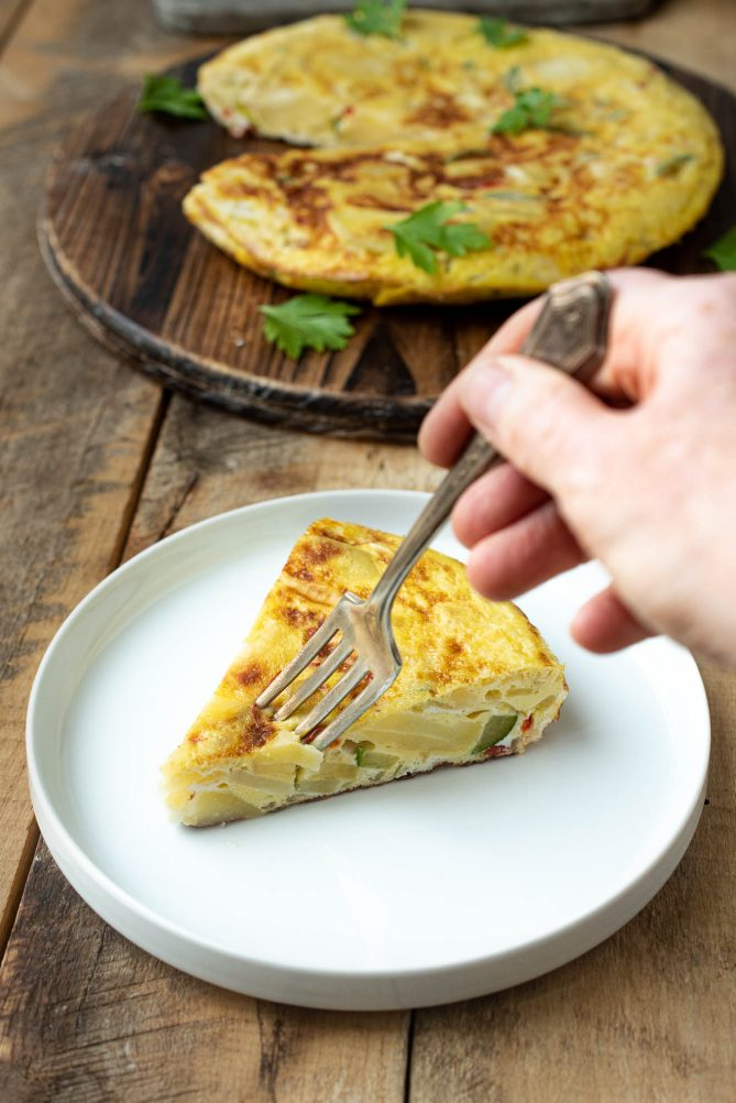 Cutting a bite with a fork from a slice of vegetable Spanish omelette tortilla
