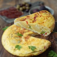 Lifting a slice of Spanish tortilla showing the potato slices, red pepper and green zucchini/courgette on the inside