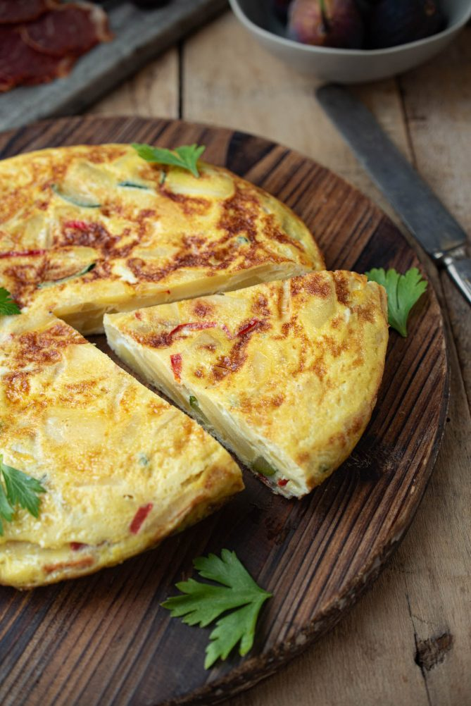 A whole Spanish omelette/tortilla on a round wood board with a triangular slice cut