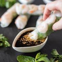 Dipping a summer shrimp spring roll into a sesame sauce