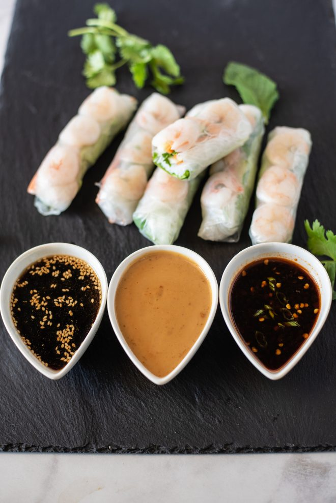 Summer shrimp vegetable rolls alongside 3 dipping sauces