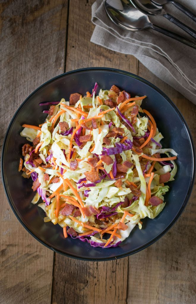 A black bowl filled with colorful warm bacon coleslaw