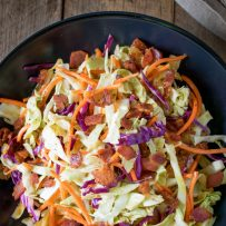 A large bowl of warm bacon coleslaw
