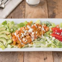 A warm buffalo chicken salad on a white rectangle plate
