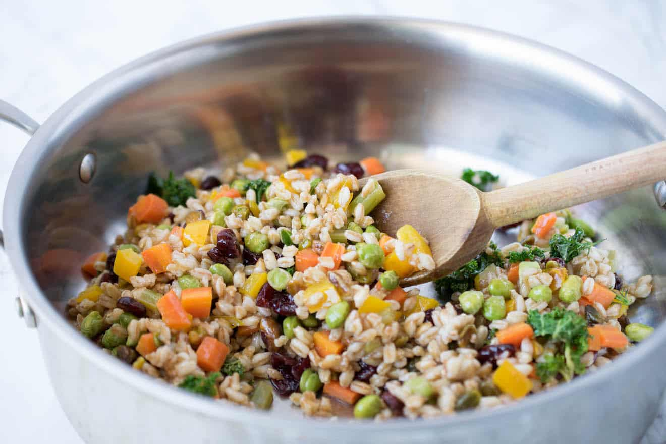 Farro and vegetables in a pan with a wooden spoon