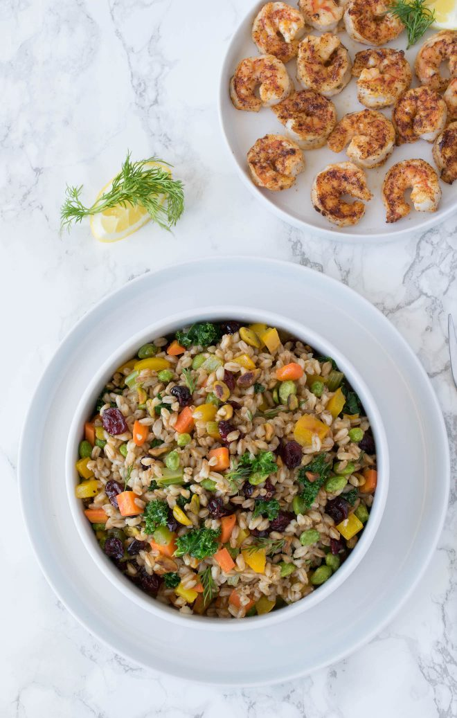 A white bowl of warm farro with cranberry and pistachios and a plate of grilled shrimp