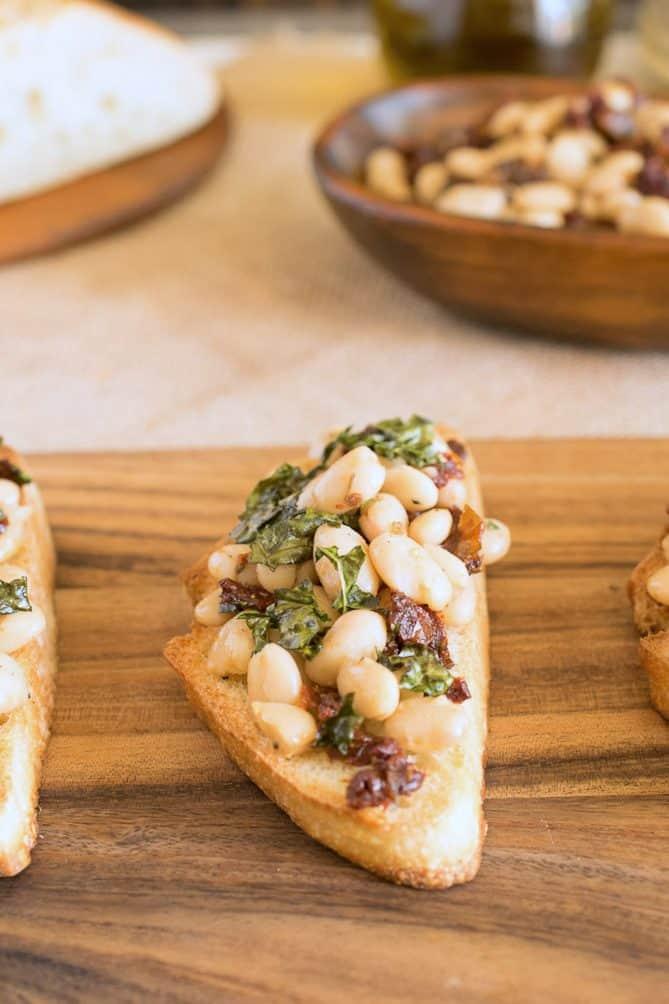 A closeup of a Tuscan bean crostini topped with crispy kale