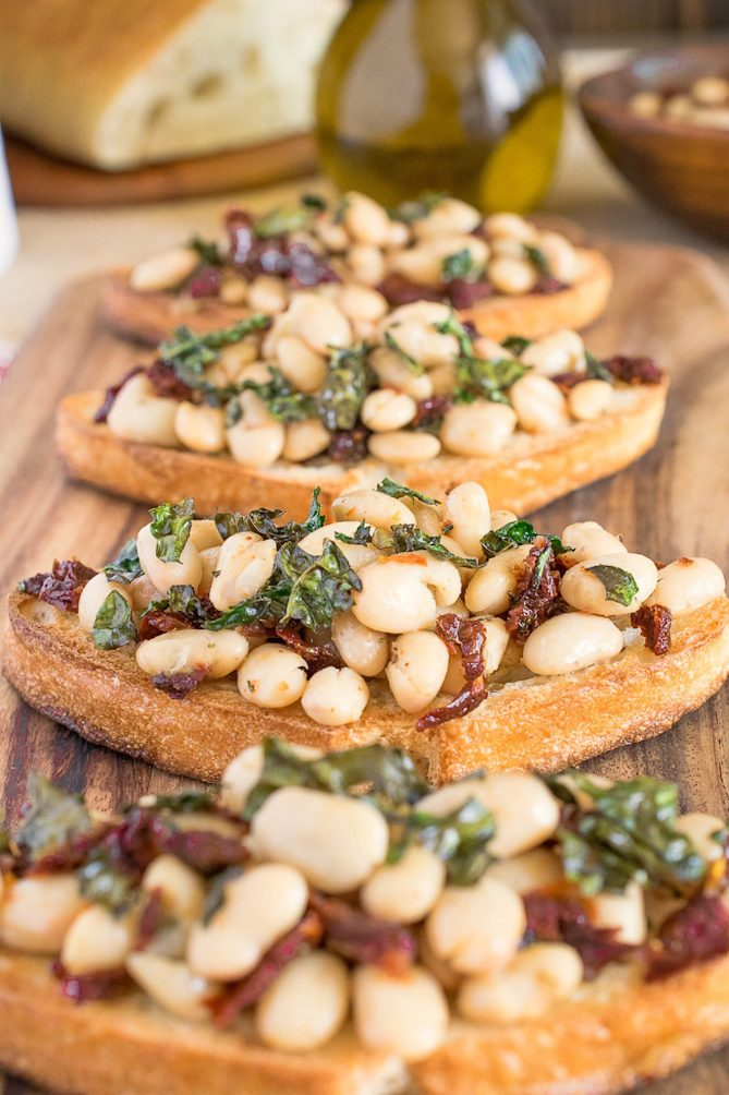 4 Warm Tuscan bean crostini lined up on a board