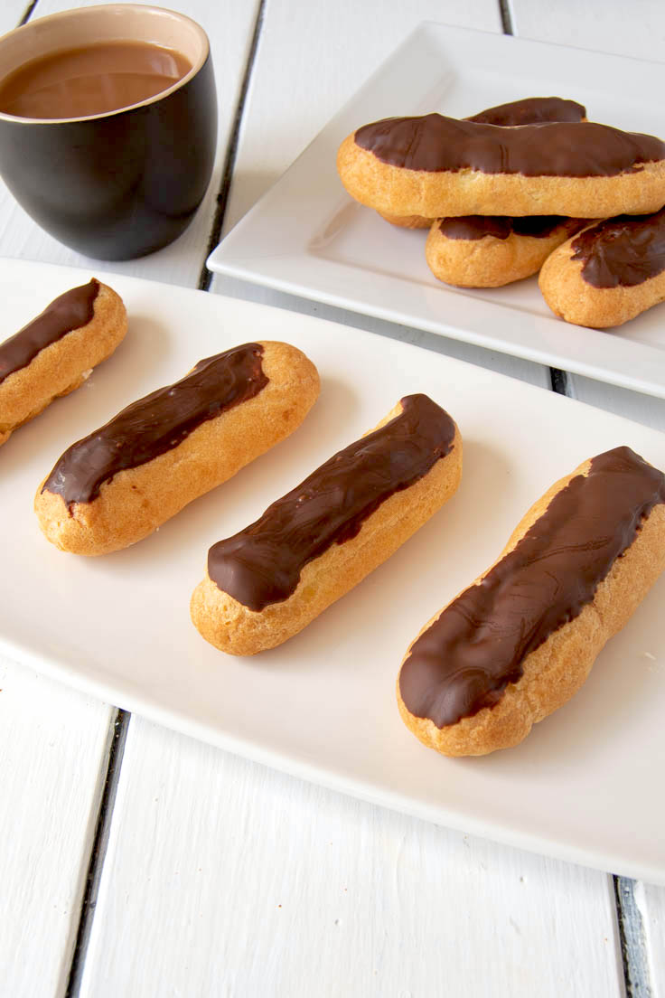 Whipped cream chocolate eclairs on a white plate with a cup of coffee