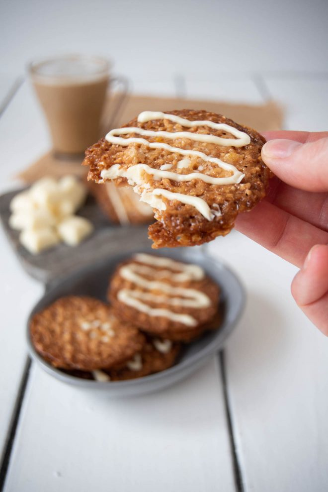 A bite take out of a white chocolate Florentine cookie