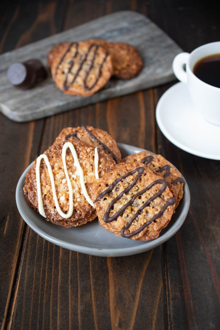 White chocolate and dark chocolate Florentine cookies on a grey plate with a cup of espresso