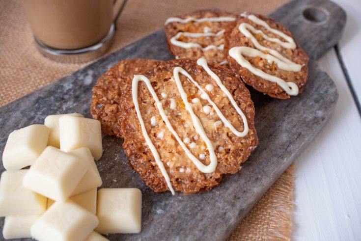 4 white chocolate Florentine cookies on a grey serving board with squares of white chocolate