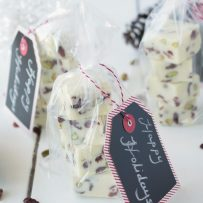 White Chocolate Pistachio Cranberry Fudge Squares wrapped in clear bags with Happy Holidays gift tags