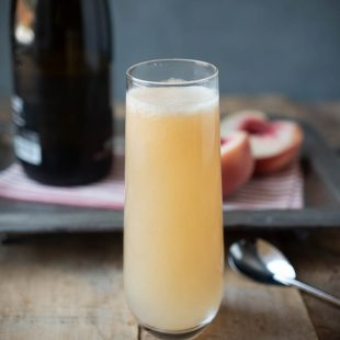 Prosecco and peach puree mixed in a stemless tall Champagne glass with a bottle of Prosecco and peach halves