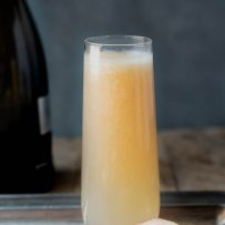 A beautiful peach hue color Bellini cocktail in a serving tray with white peach halves