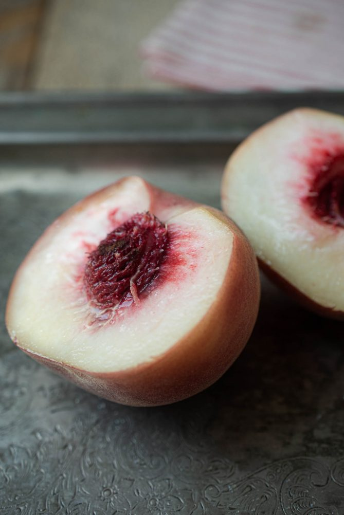 A white peach cut in half showing the white flesh with a red center and pit.