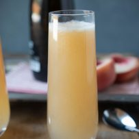 A side view of a tall glass filled with white peach Bellini