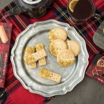 An overhead image of shortbread cookies dipping in white chocolate, lemon and pistachio on a pewter plate and tartan blanket