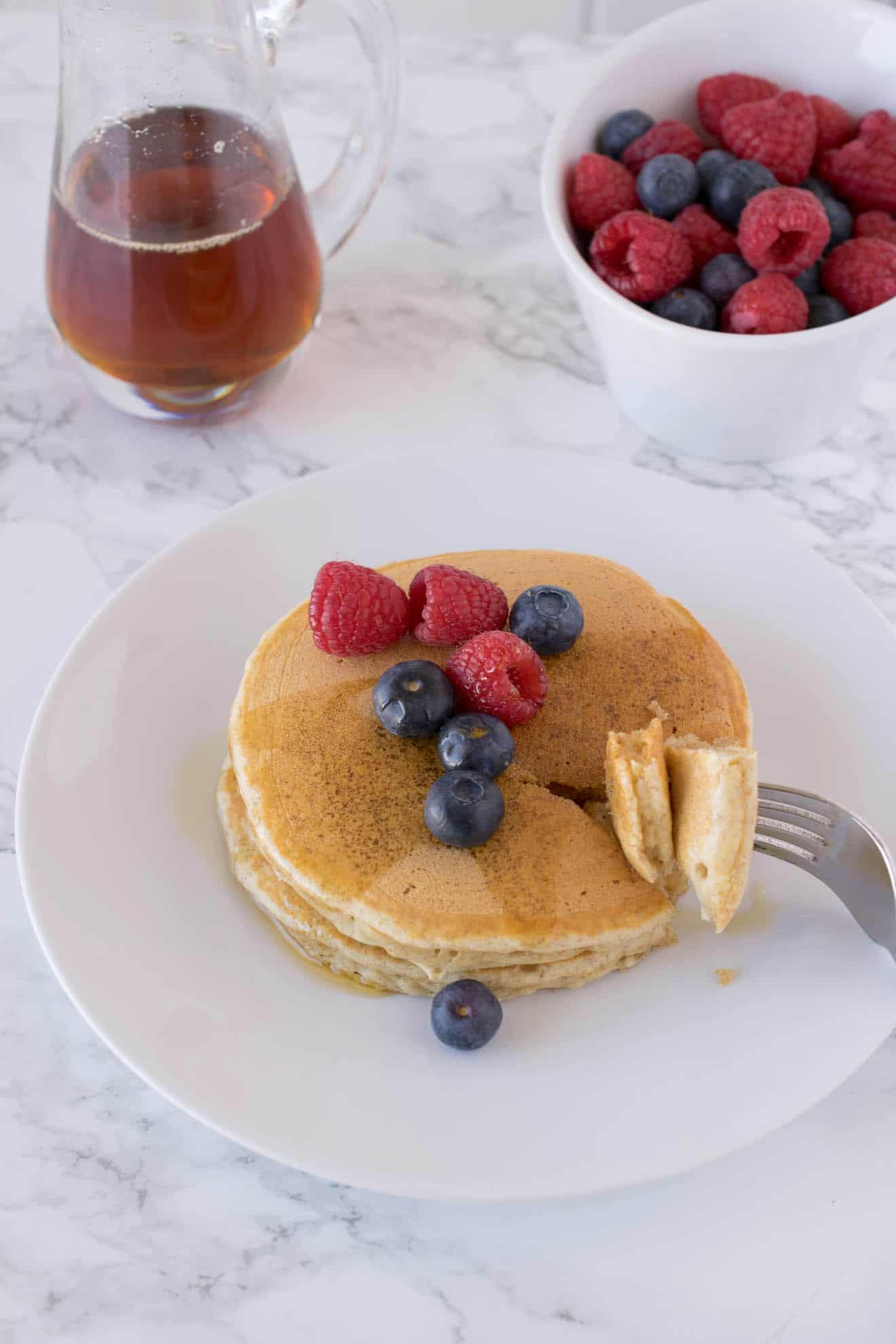 A plate of whole wheat pancakes with a bite taken out with fruit and syrup